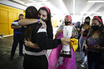 Vitarti Girl's Team driver Rocio Migliore, back to camera, arrives at pits and is embraced by friends to celebrate her second-place finish at the Oscar y Juan Galvez track in Buenos Aires, Argentina, Sunday, April 4, 2021. The racing team exclusive to females took part in the Top Race Junior series, a national competition, in Argentina for the first time. (AP Photo/Natacha Pisarenko)