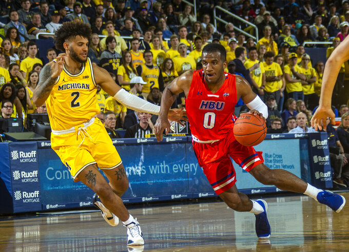 Michigan forward Isaiah Livers (2) defends against Houston Baptist guard Ian DuBose (0) during the first half of an NCAA college basketball game in Ann Arbor, Mich., Friday, Nov. 22, 2019. (AP Photo/Tony Ding)