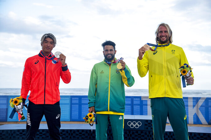 Brazil's Italo Ferreira, center, holding the gold medal, Japan's Kanoa Igarashi, left, silver medal, and Australia's Owen Wright, bronze medal, pose for photographers in the men's surfing competition at the 2020 Summer Olympics, Tuesday, July 27, 2021, at Tsurigasaki beach in Ichinomiya, Japan. (Olivier Morin/Pool Photo via AP)