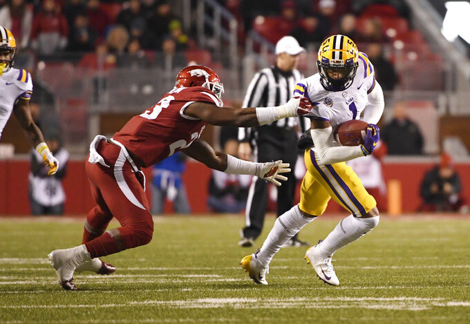 LSU receiver Ja'Marr Chase slips past Arkansas defender Dre Greenlaw during the first half of an NCAA college football game, Saturday, Nov. 10, 2018, in Fayetteville, Ark. (AP Photo/Michael Woods)