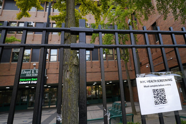 A sign posted on Oct. 2nd advises anyone entering Edward R. Murrow High School must go through a city health screening, Monday, Oct. 5, 2020, in the Midwood section of the Brooklyn borough of New York. The school is one of many in New York City that will close Tuesday after New York Gov Andrew Cuomo ordered schools in city neighborhoods with high coronavirus rates to shut down. (AP Photo/Kathy Willens)