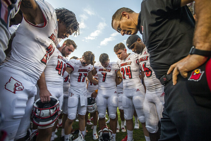 Louisville Cardinals head coach Scott Satterfield and his team pray at midfield after defeating Florida State 31-23 in an NCAA college football game in Tallahassee, Fla., Saturday, Sept. 25, 2021. (AP Photo/Mark Wallheiser)