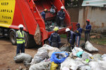 In this photo of Wednesday, July 10, 2019, workers of Kampala Capital City Authority remove garbage under a campaign encouraging people to keep their neighbourhood clean, in Makindye Lukuli area of Kampala, Uganda.  Africa faces a population boom unmatched anywhere in the world, with millions of people moving to fast-growing cities but the decades-old sanitation facilities are crumbling under the pressure.  (AP Photo/Ronald Kabuubi)