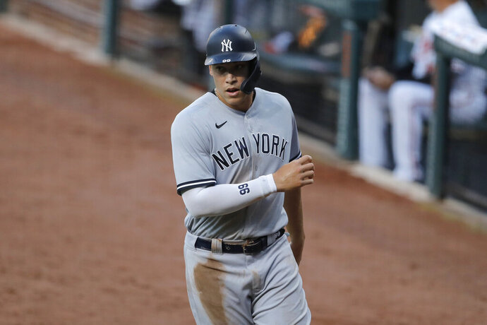 New York Yankees' Aaron Judge heads to the dugout after scoring on a sacrifice fly ball by Mike Ford off Baltimore Orioles starting pitcher Asher Wojciechowski during the first inning of a baseball game, Wednesday, July 29, 2020, in Baltimore. (AP Photo/Julio Cortez)