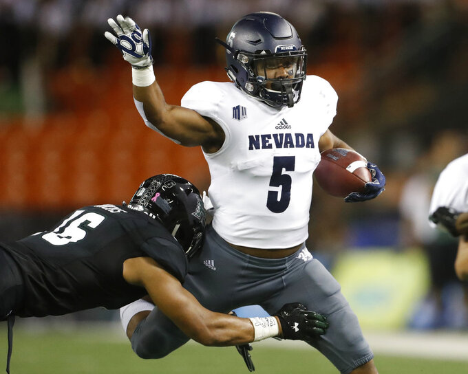 Nevada running back Jaxson Kincaide (5) gets tackled by Hawaii defensive back Kalen Hicks (16)during the second quarter of an NCAA college football game, Saturday, Oct. 20, 2018, in Honolulu. (AP Photo/Marco Garcia)