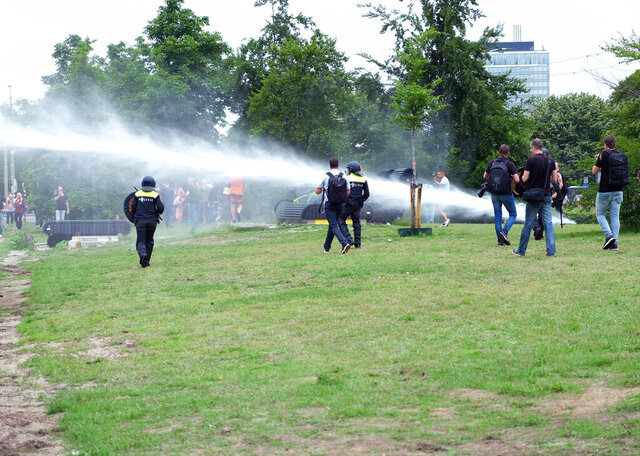 Police use a water cannon during a demonstration targeting the government's handling of the coronavirus crisis, in Malieveld, the Hague, Netherlands, Sunday, June 21, 2020. Dutch police charged hundreds of what they called soccer fans with horses and a water cannon in the center of The Hague Sunday and warned people to stay away from the city center. (AP Photo/Michael Corder)