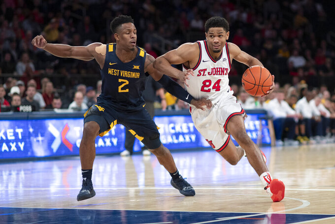 West Virginia's Brandon Knapper (2) defends against St. John's Nick Rutherford (24) in the second half of a basketball game, Saturday, Dec. 7, 2019, in New York. St. John's won 70-68. (AP Photo/Mark Lennihan)