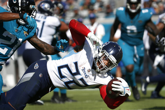Tennessee Titans running back Derrick Henry (22) dives for a touchdown past Jacksonville Jaguars cornerback Nevin Lawson (21) during the second half of an NFL football game, Sunday, Oct. 10, 2021, in Jacksonville, Fla. (AP Photo/Stephen B. Morton)