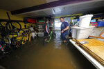 Rudy Horvath Jr., left, moves his bicycle from his home, a boat house in the West End section of New Orleans, as his father, Rudy Horvath Sr., right, looks on after it took on water from a rising storm surge from Lake Pontchartrain in advance of Tropical Storm Cristobal, Sunday, June 7, 2020. (AP Photo/Gerald Herbert)