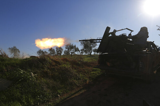 Turkish backed Syrian fighter fires at a frontline near the town of Saraqib in Idlib province, Syria, Wednesday, Feb. 26, 2020. Syrian government forces have captured dozens of villages, including major rebel strongholds, over the past few days in the last opposition-held area in the country's northwest. (AP Photo/Ghaith Alsayed)