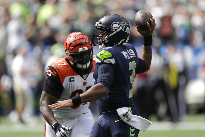 Seattle Seahawks quarterback Russell Wilson, right, passes as Cincinnati Bengals defensive tackle Geno Atkins, left, closes in during the first half of an NFL football game Sunday, Sept. 8, 2019, in Seattle. (AP Photo/Stephen Brashear)