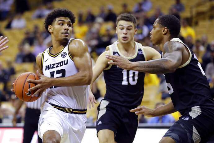 Missouri's Mark Smith, left, heads to the basket as Wofford's Nathan Hoover (10) and Messiah Jones defend during the second half of an NCAA college basketball game Monday, Nov. 18, 2019, in Columbia, Mo. (AP Photo/Jeff Roberson)