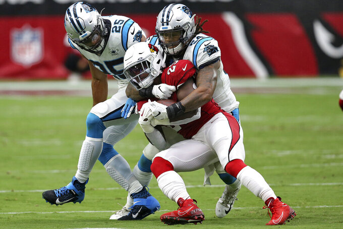 Carolina Panthers cornerback Javien Elliott (23) is tackled by Carolina Panthers outside linebacker Shaq Thompson (54) and strong safety Eric Reid (25) during the first half of an NFL football game, Sunday, Sept. 22, 2019, in Glendale, Ariz. (AP Photo/Ross D. Franklin)
