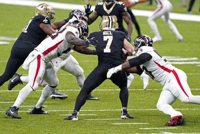 New Orleans Saints quarterback Taysom Hill (7) is sacked by Atlanta Falcons defensive end Allen Bailey, left, and defensive tackle Grady Jarrett in the first half of an NFL football game in New Orleans, Sunday, Nov. 22, 2020. (AP Photo/Butch Dill)