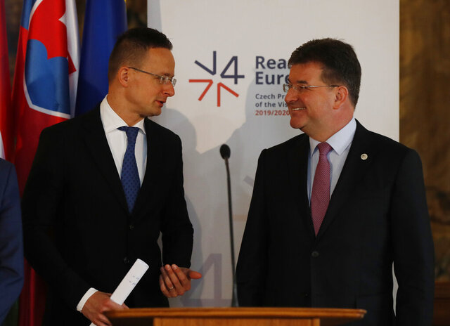 Foreign Minister of Slovakia Miroslav Lajcak, right, talks to his Hungary's counterpart Peter Szijjarto, left, during their joint press in Prague, Czech Republic, Monday, Dec. 2, 2019. (AP Photo/Petr David Josek)