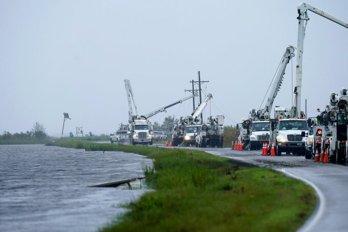 Utility crews replace power poles destroyed by Hurricane Ida as Tropical Storm Nicholas approaches in Pointe-aux-Chenes, La., Tuesday, Sept. 14, 2021. (AP Photo/Gerald Herbert)