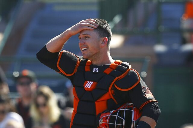FILE - In this Monday, Feb. 24, 2020, file photo, San Francisco Giants catcher Buster Posey wipes sweat from his forehead during the first inning of a spring training baseball game against the Arizona Diamondbacks in Scottsdale, Ariz. Posey is the latest big-name player to skip this season because of concerns over the coronavirus pandemic. Posey announced his decision on Friday, July 10, 2020. He says his family finalized the adoption of identical twin girls this week. The babies were born prematurely and Posey said after consultations with his wife and doctor he decided to opt out of the season. (AP Photo/Ross D. Franklin, File)