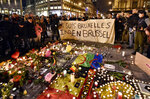 """FILE - In this March 22, 2016 file photo people holding a banner reading """"I am Brussels"""" behind flowers and candles to mourn for the victims at Place de la Bourse in the center of Brussels. Bombs exploded at the Brussels airport and one of the city's metro stations Tuesday, killing and wounding scores of people, as a European capital was again locked down amid heightened security threats. (AP Photo/Martin Meissner, File)"""