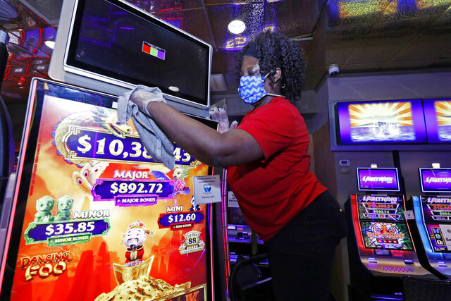 Annette Smith with housekeeping, sports a special WaterView Casino and Hotel mask and gloves as he cleans one of the video gaming machines throughout the Vicksburg, Miss., gaming establishment, Wednesday, May 20, 2020. Employees are cleaning and sanitizing before opening their doors Thursday morning, May 21, following a two-month shutdown due to coronavirus. Patrons will notice a number of changes including the limiting of players at any gaming table, at least six-feet of spacing between tables and video or slot machines, and the requirement of all casino employees to wear face masks and be screened before being allowed into the building.  (AP Photo/Rogelio V. Solis)