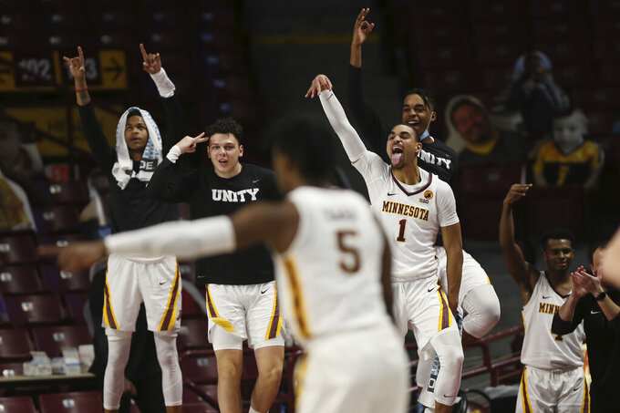 Minnesota players, including Minnesota's Tre' Williams (1), celebrate courtside after their team scored against Michigan State during the second half of an NCAA college basketball game, Monday, Dec. 28, 2020, in Minneapolis. Minnesota won 81-56. (AP Photo/Stacy Bengs)