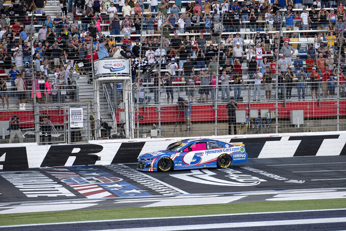 Kyle Larson (5) takes the checkered flag during a NASCAR Cup Series auto racing race at Charlotte Motor Speedway, Monday, Oct. 11, 2021, in Concord, N.C. (AP Photo/Matt Kelley)