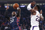 Phoenix Suns center Deandre Ayton (22) keeps his distance as New York Knicks forward Julius Randle (30) takes a shot during the first quarter of an NBA basketball game in New York, Thursday, Jan. 16, 2020. (AP Photo/Kathy Willens)