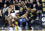 Memphis' Alex Lomax tries to gather the ball against Wichita State's Grant Sherfield, left, Morris Udeze, center, and Trey Wade during the first half of an NCAA college basketball game Thursday, Jan. 9, 2020, in Wichita, Kan. (Travis Heying/The Wichita Eagle via AP)