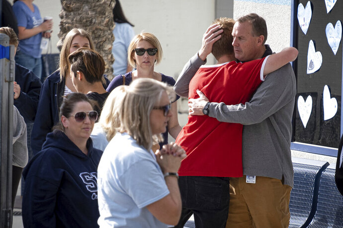 Saugus high principal Vince Ferry, right, gives hugs and welcomes students back on campus Tuesday, Nov. 19, 2019. Students were allowed back to collect their belongings left behind after the tragic shooting last Thursday. Classes will resume at the high school on Dec. 2. (David Crane/The Orange County Register via AP)