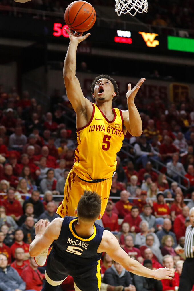 Iowa State guard Lindell Wigginton, top, is fouled by West Virginia guard Jordan McCabe while driving to the basket during the second half of an NCAA college basketball game Wednesday, Jan. 30, 2019, in Ames, Iowa. Wigginton scored 27 points as Iowa State won 93-68. (AP Photo/Charlie Neibergall)