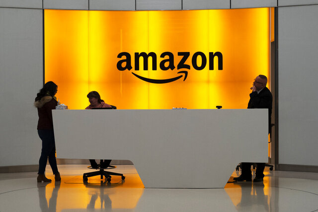 """FILE - In this Feb. 14, 2019 file photo, people stand in the lobby for Amazon offices in New York.  The United States for the first time added five of Amazon's overseas operations to its list of """"notorious markets'' where pirated goods are sold.   Trade Representative on Wednesday, April 29, 2020 added the Amazon domains in Canada, France, Germany, India and the United Kingdom to its annual blacklist.  (AP Photo/Mark Lennihan, File)"""