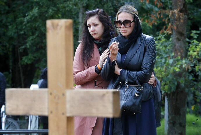 Two women mourn at the grave of one of the 14 crew members who died in a fire on a Russian navy's deep-sea research submersible, at the Serafimovskoye memorial cemetery during a funeral ceremony in St. Petersburg, Russia, Saturday, July 6, 2019. Russian President Vladimir Putin has awarded the nation's highest honors to 14 seamen who died in a fire on one of the navy's research submersibles. (AP Photo/Dmitri Lovetsky)