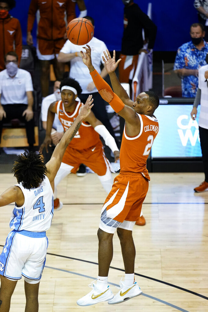 Texas guard Matt Coleman III (2) shoots for the winning basket over North Carolina guard R.J. Davis (4) in the second half of an NCAA college basketball game for the championship of the Maui Invitational, Wednesday, Dec. 2, 2020, in Asheville, N.C. Texas won 69-67. Coleman was awarded the MVP. (AP Photo/Kathy Kmonicek)