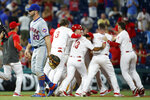 New York Mets first baseman Pete Alonso, left, walks off the field as the Philadelphia Phillies celebrate a double by Jay Bruce that drove in the winning run during the 10th inning of a baseball game Wednesday, June 26, 2019, in Philadelphia. Philadelphia won 5-4. (AP Photo/Matt Slocum)
