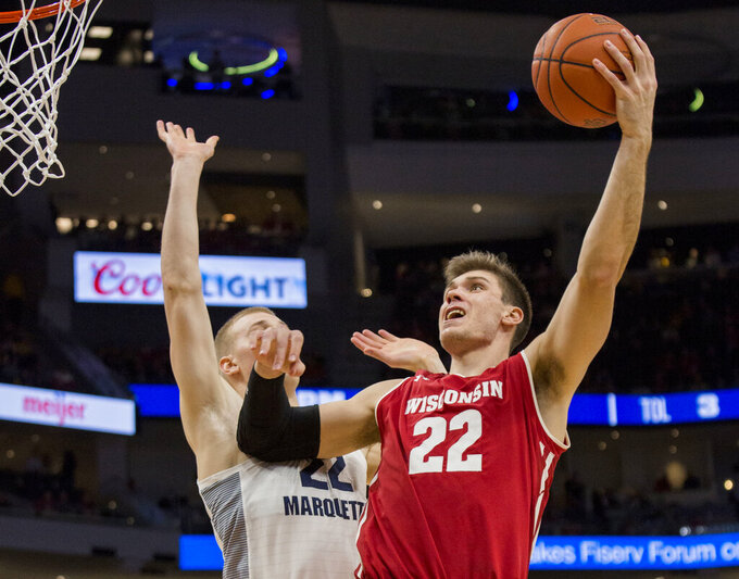 FILE - In this Dec. 8, 2018, file photo, Wisconsin forward Ethan Happ, right, goes up for a basket against Marquette forward Joey Hauser during the second half of an NCAA college basketball game, in Milwaukee. Happ was named to the AP All-Big Ten Conference team, Tuesday, March 12, 2019. (AP Photo/Darren Hauck, File)