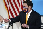 Arizona Republican Gov. Doug Ducey uses hand sanitizer as he wears a face covering prior to speaking about the latest coronavirus data at a news conference Thursday, June 25, 2020, in Phoenix. (AP Photo/Ross D. Franklin, Pool)
