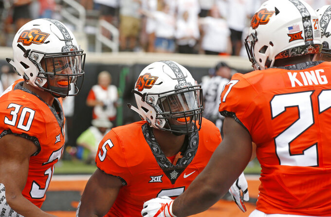 Oklahoma State running back Justice Hill (5) celebrates a touchdown against Boise State with teammates Chuba Hubbard (30) and J.D. King (27) in the first half of an NCAA college football game in Stillwater, Okla., Saturday, Sept. 15, 2018. (AP Photo/Sue Ogrocki)