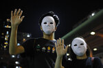 Masked protesters hold up their hands to represent their five demands in Hong Kong on Saturday, Oct. 5, 2019. All subway and train services were suspended, lines formed at the cash machines of shuttered banks, and shops were closed as Hong Kong dusted itself off and then started marching again Saturday after another night of rampaging violence decried as