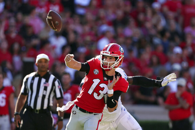 Georgia quarterback Stetson Bennett (13) fumbles the ball as Kentucky defensive end Josh Paschal (4) hits him during the first half of an NCAA college football game Saturday, Oct. 16, 2021 in Athens, Ga. (AP Photo/Butch Dill)
