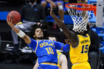 UCLA guard Tyger Campbell (10) shoots over Michigan guard Chaundee Brown (15) during the second half of an Elite 8 game in the NCAA men's college basketball tournament at Lucas Oil Stadium, Tuesday, March 30, 2021, in Indianapolis. (AP Photo/Darron Cummings)