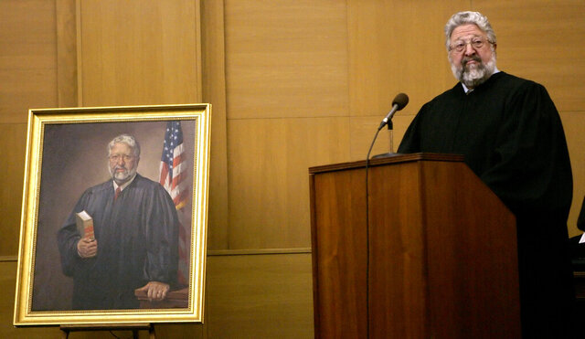 FILE - In this Jan. 12, 2007, file photo, U.S. District Judge Dominic Squatrito speaks at a ceremony where his portrait was displayed and observing his change in status to a senior judge, in Hartford, Conn. Judge Squatrito, a Manchester native and Fulbright scholar who served on the federal court bench for more than 25 years, has died at age 82. Federal court officials say Squatrito died Wednesday, Jan. 20, 2021. (AP Photo/Bob Child, File)