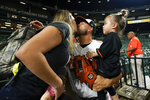 Baltimore Orioles relief pitcher Manny Barreda, center, greets his daughter, Sofia, 2, and his wife, Karla Torres, after he recorded the win during his professional debut in a baseball game against the Kansas City Royals, Wednesday, Sept. 8, 2021, in Baltimore. The Orioles won 9-8. (AP Photo/Julio Cortez)