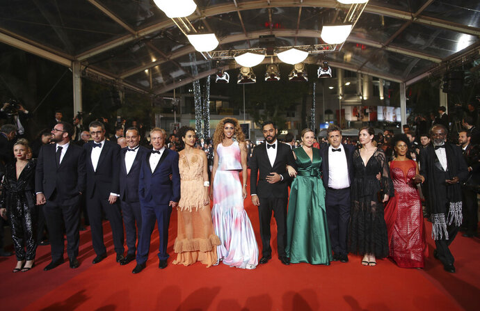 Co director Juliano Dornelles, second from left, actors Udo Kier fifth from left, Babara Colen, sixth from left, Silveiro Peirera, seventh from left and co director Kleber Mendonca Filho, tenth from left pose for photographers upon arrival at the premiere of the film 'Bacurau' at the 72nd international film festival, Cannes, southern France, Wednesday, May 15, 2019. (AP Photo/Petros Giannakouris)