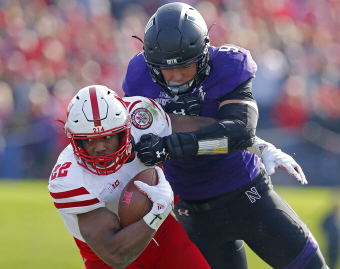 Nebraska's Devine Ozigbo, left, is tackled by Northwestern's Samdup Miller during the second half of an NCAA college football game, Saturday, Oct. 13, 2018, in Evanston, Ill. (AP Photo/Jim Young)