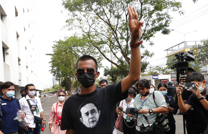 In this Monday, March 8, 2021, photo, pro-democracy activist Panupong Jadnok raises a three-finger symbol of resistance as he arrived at the Attorney General's office in Bangkok, Thailand. A court in Thailand on Tuesday agreed to release Panupong, one of two key leaders of the anti-government protest movement, on bail on the condition that he refrains from activities deemed to defame the monarchy. Panupong must also wear electronic tags and is banned from leaving the country. (AP Photo/Sakchai Lalit)