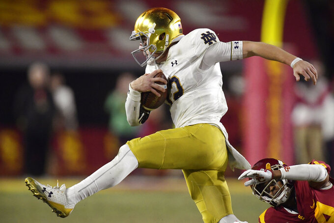 Notre Dame quarterback Ian Book, left, avoids a tackle by Southern California cornerback Isaiah Langley during the second half of an NCAA college football game Saturday, Nov. 24, 2018, in Los Angeles. Notre Dame won 24-17. (AP Photo/Mark J. Terrill)