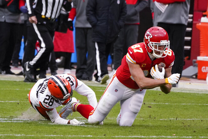 Kansas City Chiefs tight end Travis Kelce (87) catches a pass in front of Cleveland Browns cornerback Kevin Johnson (28) during the first half of an NFL divisional round football game, Sunday, Jan. 17, 2021, in Kansas City. (AP Photo/Charlie Riedel)