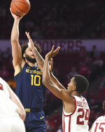 West Virginia guard Jermaine Haley (10) shoots the ball over Oklahoma guard Jamal Bieniemy (24) during the first half of an NCAA college basketball game in Norman, Okla., Saturday, Feb. 8, 2020. (AP Photo/Kyle Phillips)