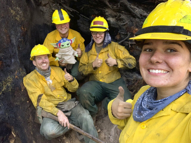 "Lucas Galloway, from left, Jaebyn Drake, Rhett Schieder and Audrey Wilcox pose for a selfie with Baby Yoda on Sept. 20, 2020, while fighting the Holiday Farm Fire in Blue River, Oregon. Beleaguered firefighters in the western United States have a new force on their side: Baby Yoda. In early September, A 5-year-old Oregon boy named Carver and his grandmother delivered a toy version of ""The Mandalorian"" character to a donation center for firefighters. The toy came with a handwritten note from Carver saying the toy was meant to be ""a friend"" in case they got lonely. Since then, Baby Yoda has been to four wildfires in two states. (Courtesy of Audrey Wilcox via AP)"