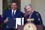 Gov. Ron DeSantis, left, presents former Florida State University NCAA college football coach Bobby Bowden, right, with the Governor's Medal of Freedom at the Governor's Mansion in Tallahassee, Fla., Wednesday, April 7, 2021. (Tori Lynn Schneider/Tallahassee Democrat via AP)