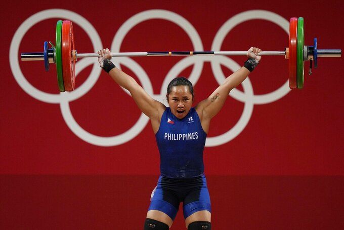 Hidilyn Diaz of Philippines competes in the women's 55kg weightlifting event, at the 2020 Summer Olympics, Monday, July 26, 2021, in Tokyo, Japan. (AP Photo/Luca Bruno)